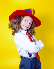 Happy child wearing bright colorful hat on yellow background