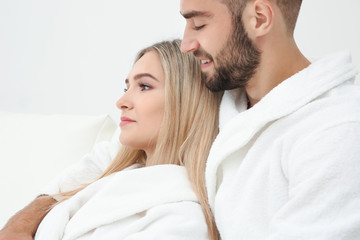 Young couple in bathrobes relaxing, closeup