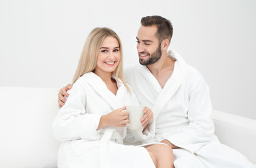 Young couple in bathrobes relaxing on sofa