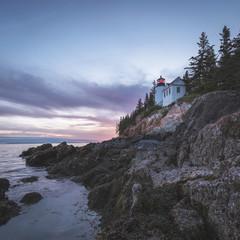 House on cliff near ocean at sunset