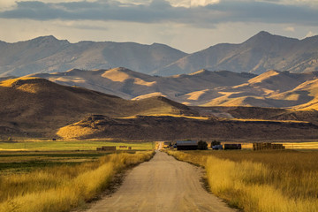 Dirt road to farm and mountains