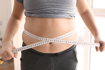 Overweight boy measuring his waist at home, closeup