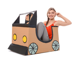 Young woman playing with cardboard auto against white background. Concept of buying new car