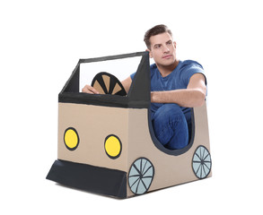 Young man playing with cardboard auto against white background. Concept of buying new car