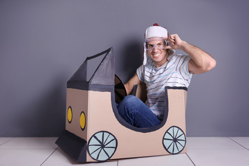 Young woman playing with cardboard auto near grey wall. Concept of buying new car