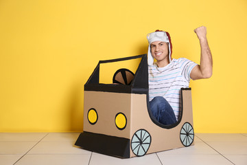 Young man playing with cardboard auto near color wall. Concept of buying new car