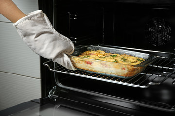Woman taking glass baking dish with delicious casserole from oven, closeup
