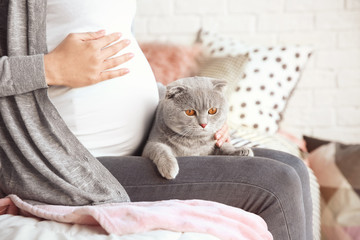 Pregnant young woman with cute pet cat on bed at home