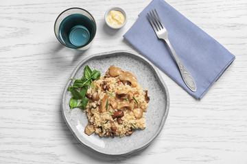Plate with delicious risotto and mushrooms on table