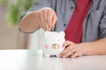 Young man putting coin into piggy bank at table indoors