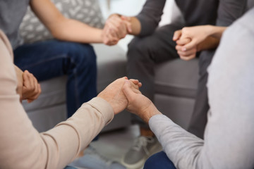 Young people holding hands during group therapy, closeup