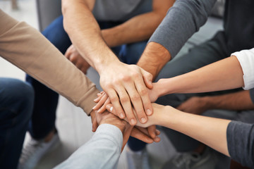 Young people putting hands together during group therapy, closeup