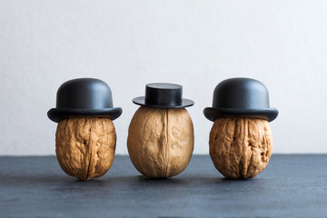 Gentleman walnuts black hats on stone and gray background. Creative food design poster. Macro view selective focus photo