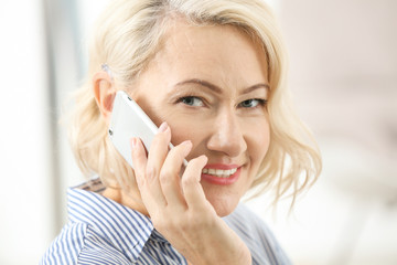 Mature woman with hearing aid talking on cell phone indoors