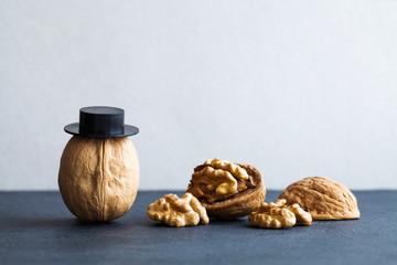 Senor walnuts black hats, half nutshell on stone and gray background. Creative food design poster. Macro view selective focus photo