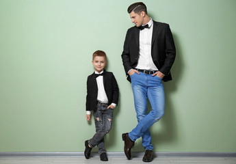Stylish father and son in jackets against color wall
