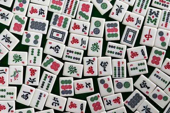 White-green tiles for mahjong on on green cloth background