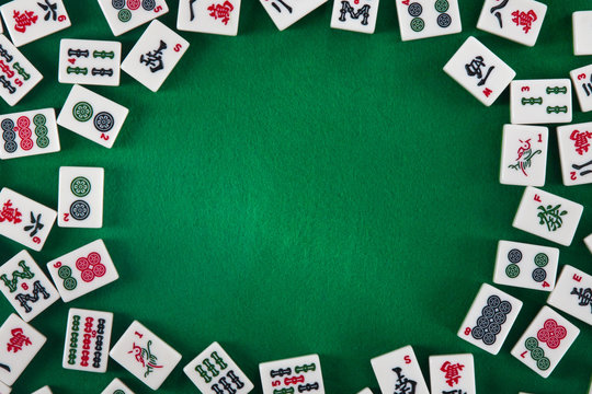 White-green tiles for mahjong on a brown wooden background. Blank space on the right