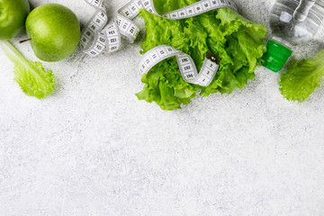 Healthy eating. Green apple, lettuce salad, water bottle, measuring tape. Dieting, slimming and weigh loss concept. Copy space and top view