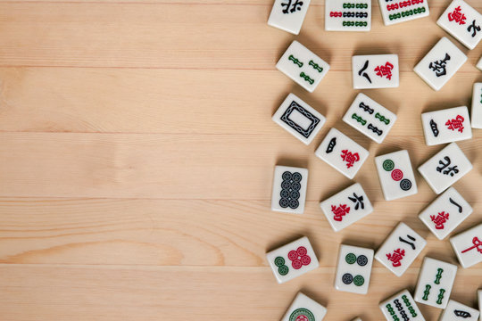 White-green tiles for mahjong on a brown wooden background. Empty space on the left