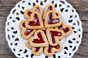 Many heart cookies in a plate on table