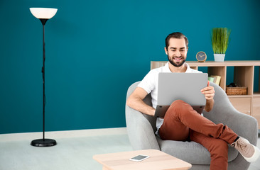 Handsome man with laptop sitting in comfortable armchair at home