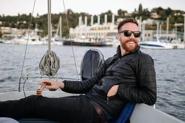 Man in sunglasses drives sailboat at sunset