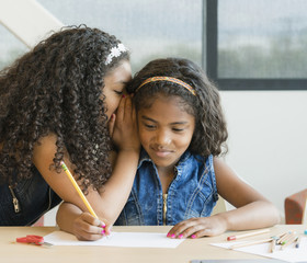 Mixed race girl whispering to sister writing on paperwork