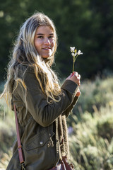 Portrait of smiling Caucasian girl holding wildflower
