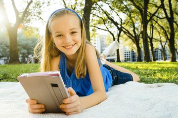 Smiling Caucasian girl laying on blanket in park reading digital tablet