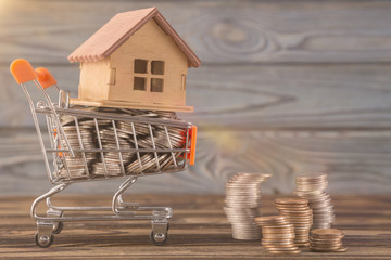The concept of a house in a shopping cart on a background of natural wood and coins, money. Idea: buying a house, renting, selling real estate. Mortgage. Loan for housing. Eco-friendly housing