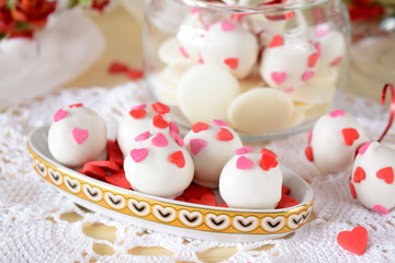 White chocolate sweets and cake pops decorated with little confectionery hearts