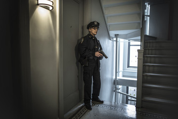 Older Caucasian policewoman holding gun in apartment staircase