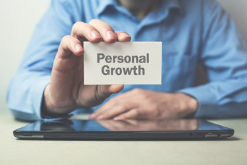 Businessman showing Personal Growth text on business card.
