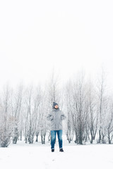 a man in a gray jacket in a winter forest