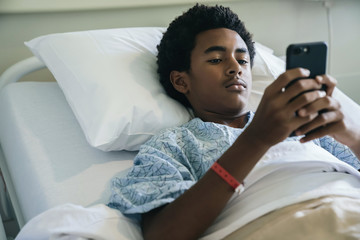 Black boy laying in hospital bed texting on cell phone