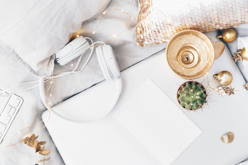 Flat lay composition with gold candle, laptop, headphones and white blank. Freelance composition