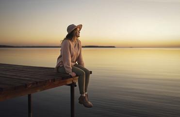 Woman sitting on dock of lake admiring sunset