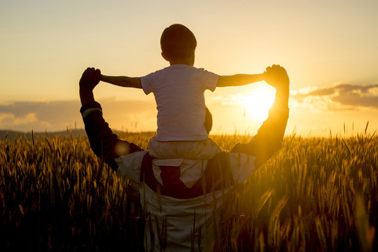 Father carrying son on shoulders in field of wheat at sunset