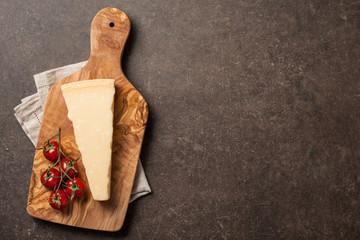 Parmesan cheese and tomatoes on wooden cutting board