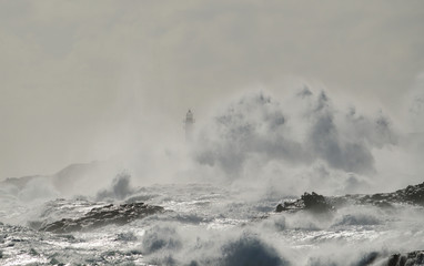 Rough sea, big wave when breaking on the coast and silhouette of lighthouse in background, Telde, Canary islands