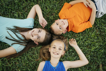 Close up portrait of smiling Caucasian brother and sisters laying on grass
