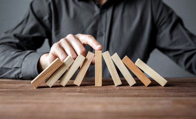 Businessman stopping domino effect with his finger. Security and insurance concept.