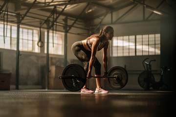 Fitness model performing weight lifting exercise at gym