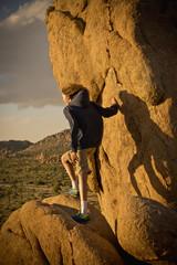 Mixed race boy standing on rock in desert