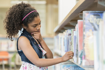 Pensive mixed race girl choosing book in library