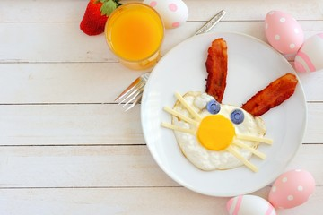 Easter breakfast with cute bunny face made of egg and bacon. Table scene, above view over a white wood background.