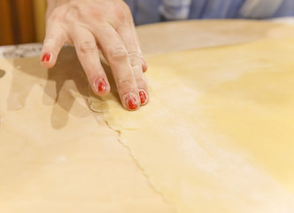 Female hand cutting dough