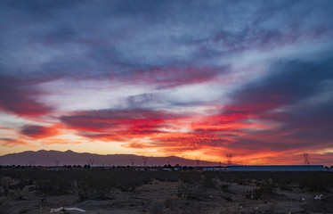 4K Sunset in the Desert with Mountains Landscape and Buildings and Red Yellow Orange Purple Sky and Clouds