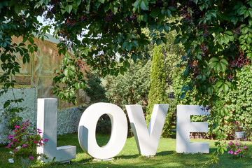 Big white letters Love on green grass in the garden outdoors, free space. Wedding decorations, romantic holiday decor. Love sign at wedding reception. Valentines day background. Love concept